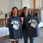 Class of 1980's Nancy (Simeona) Brenner and Ellie (Pauole) Keola show off their exclusive Kamehameha Schools alumni shirts.