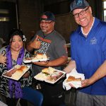 Brenda Crabbe-Jones, KSK '83, Steven Chun, KSK '84, and Michael Crabbe-Jones show off their prime rib and salmon buffet plates and famous Kamehameha brownies.